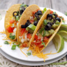 Three plated egg white tacos topped with olives, chives, tomatoes, and cheese garnished with lime and cilantro.