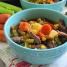 Bowl of Instant Pot Vegetable Beef Soup with fresh carrots and celery in background.