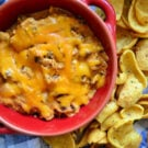 Top view of Chili Cheese Dip in a red bowl served with side of fritos.