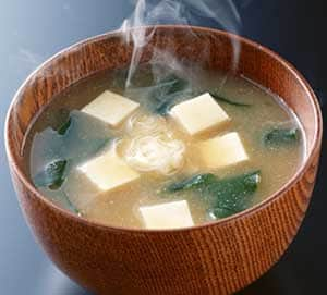 Tofu, seaweed, and miso broth steaming in wooden bowl.