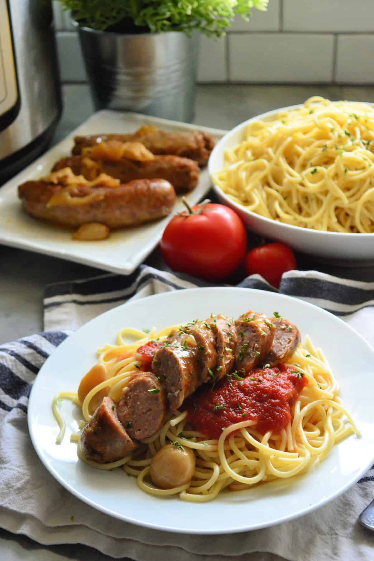 plated spaghetti with marinara and italian sausage in front of spaghetti bowl and sausage platter.