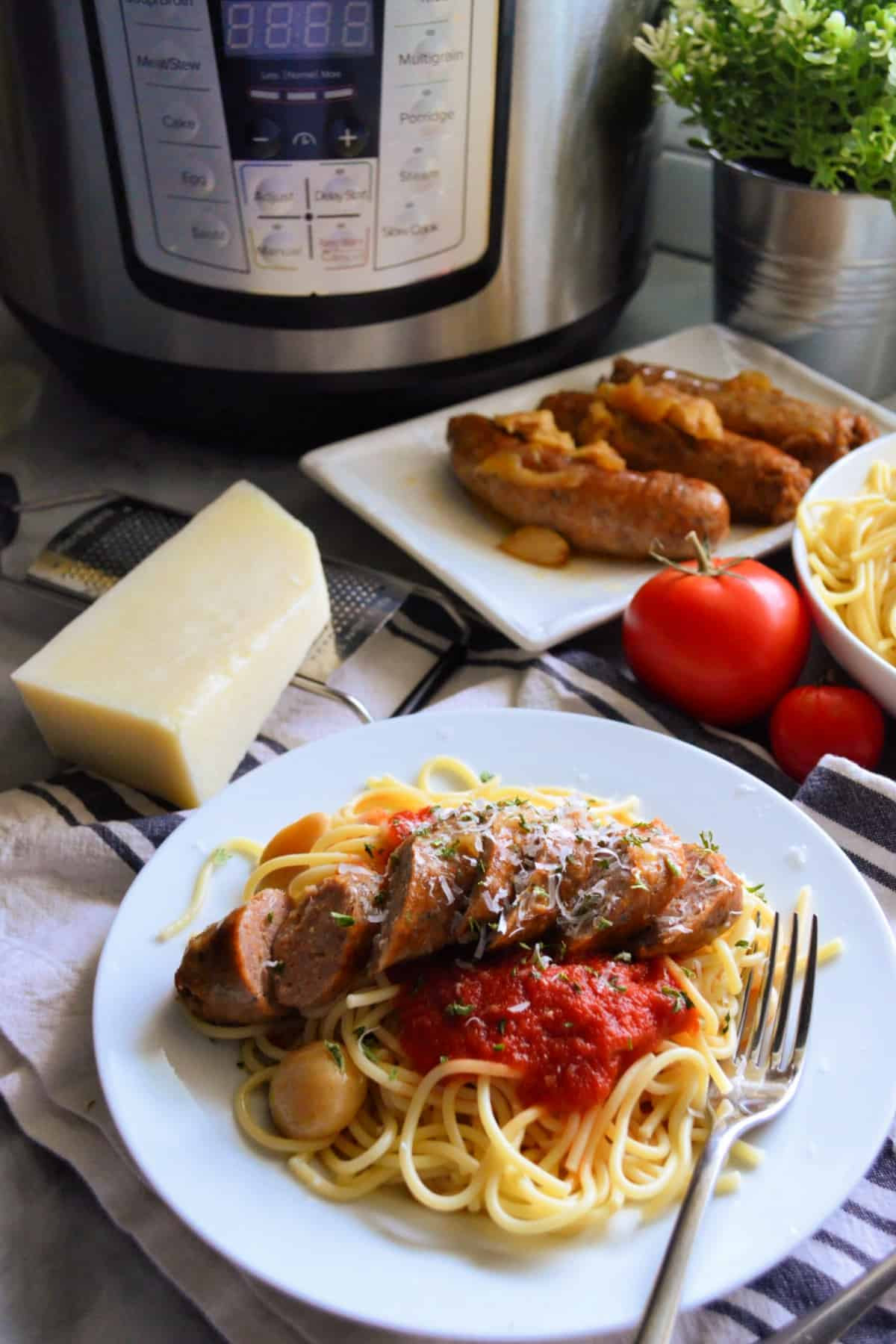 Instant Pot Italian Sausage on a plate of pasta with red sauce.