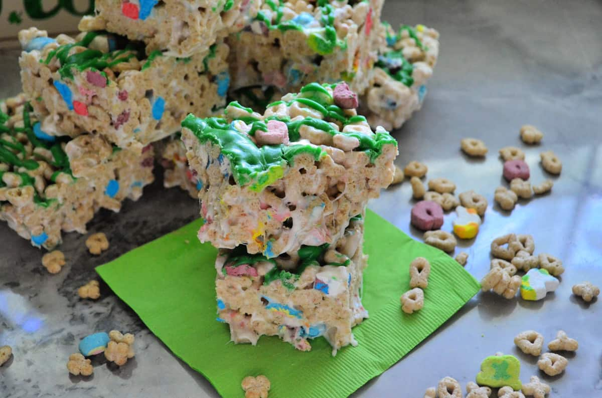 lucky charms cereal treats cut into cubes, drizzled with green chocolate, and stacked on napkin.