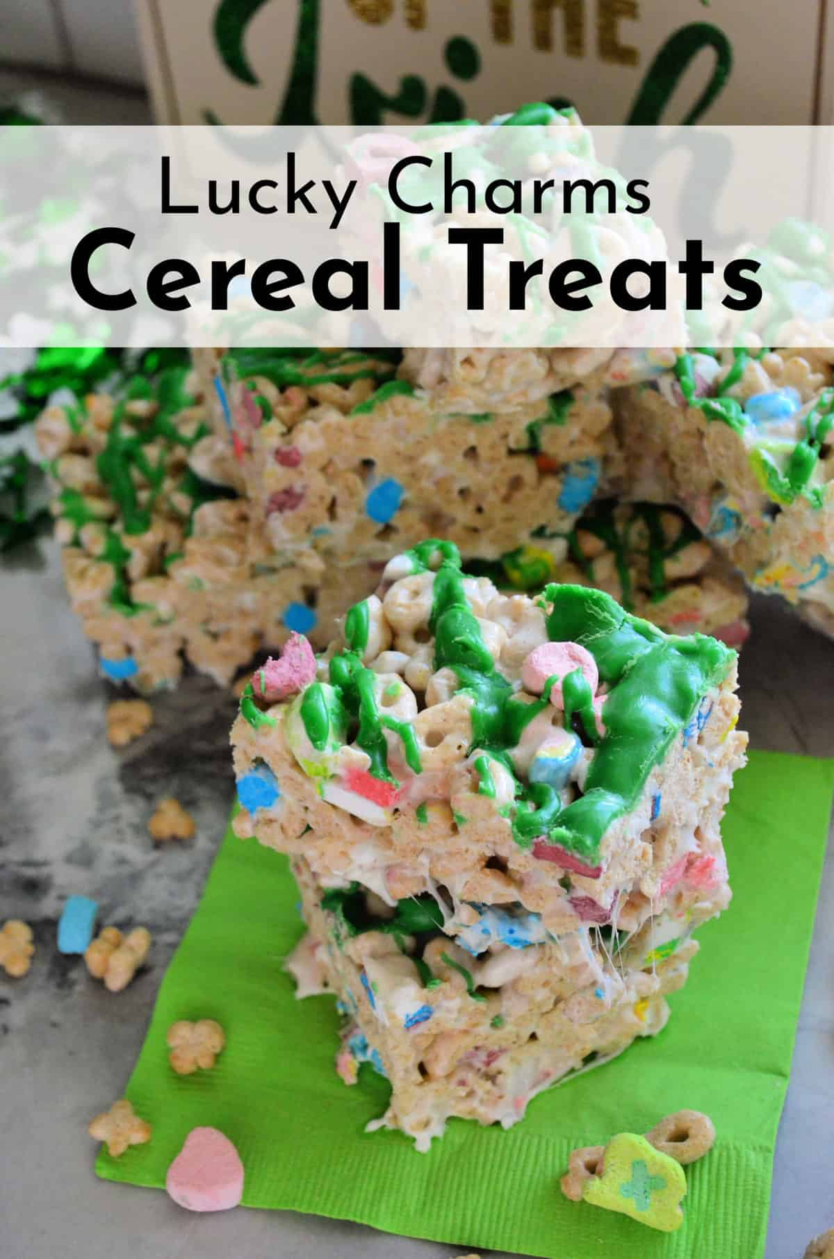 lucky charms cereal treats cut into cubes, drizzled with green chocolate, and stacked with title text.