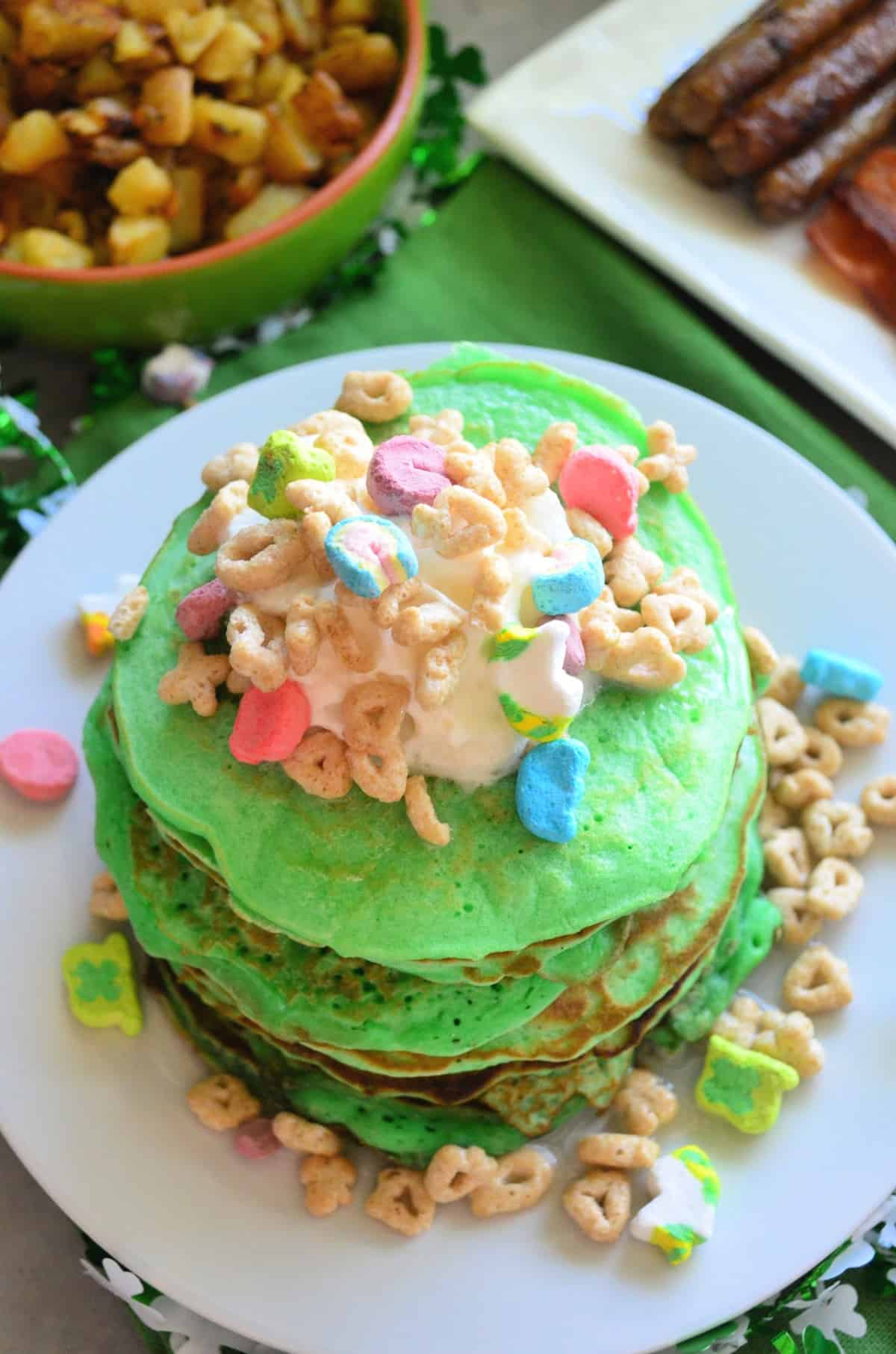 top view of stacked green pancakes topped with melted marshmallow and lucky charms on white plate.
