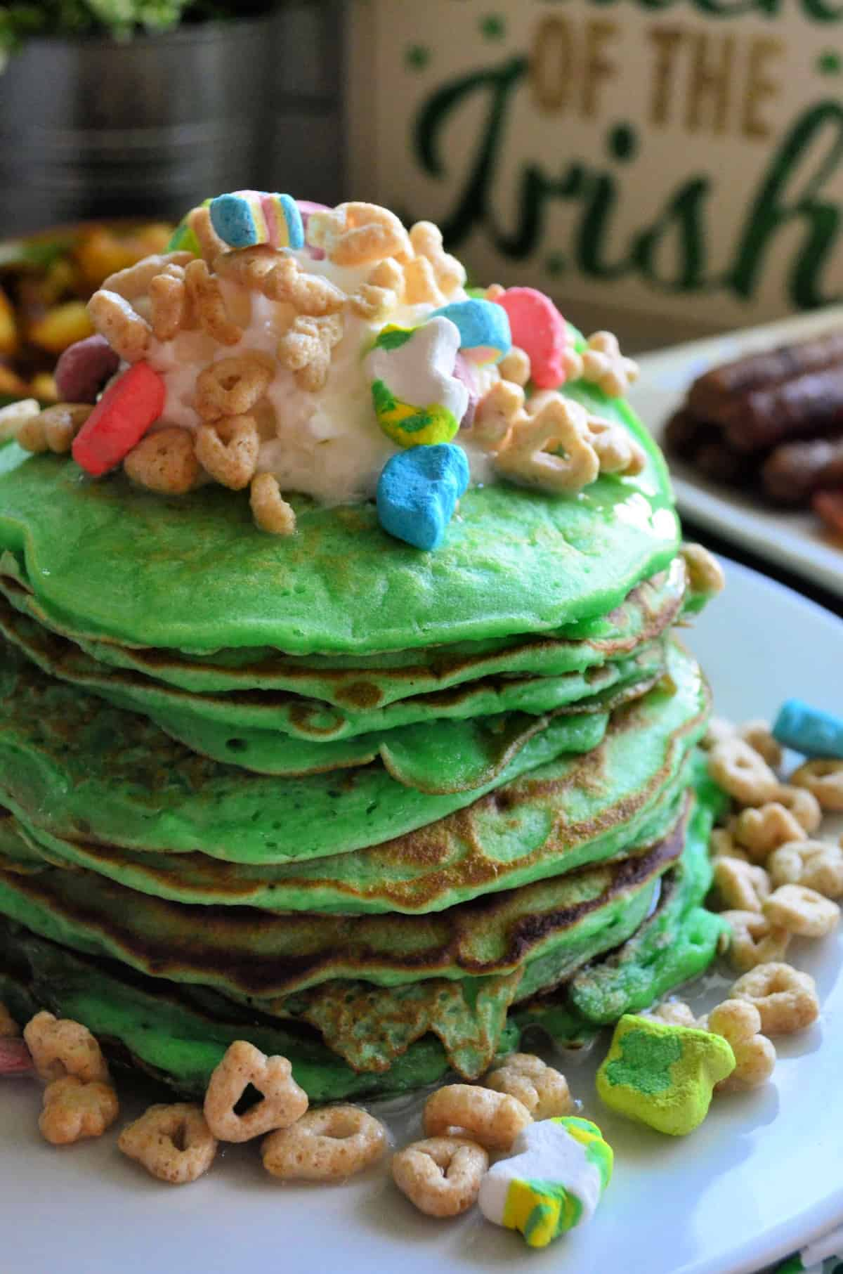 close up side view of plated stacked green pancakes topped with lucky charms with sausage in background.