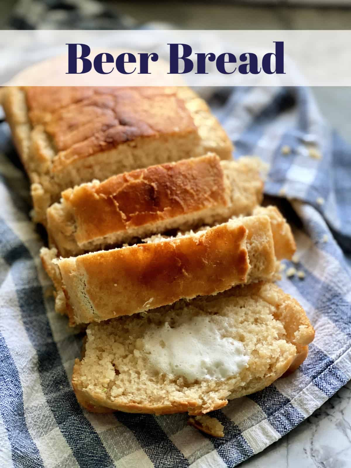 Sliced loaf of Beer Bread resting on tablecloth with title text.