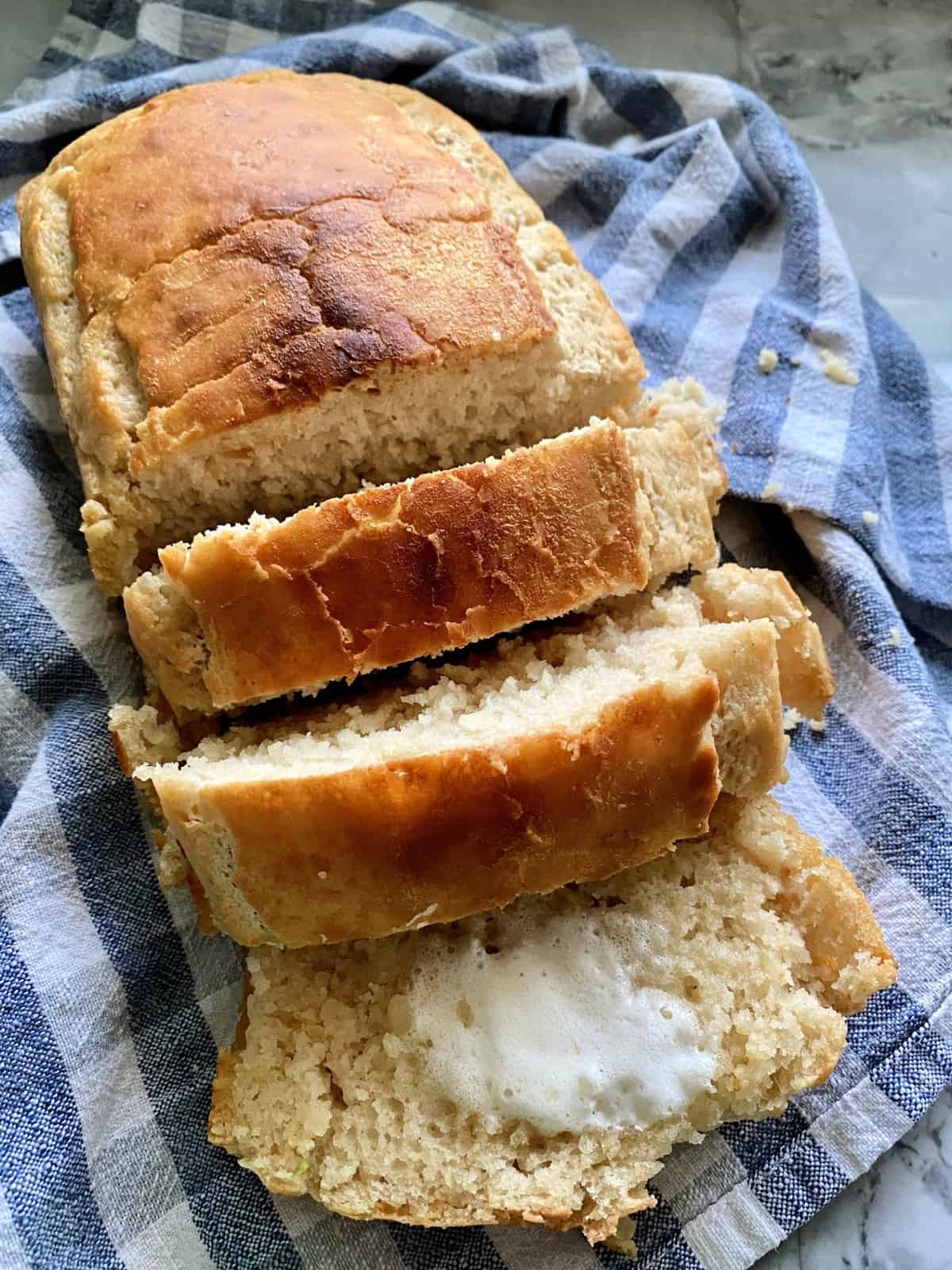 Loaf of beer bread with a few slices cut and falling away from loaf on blue tablecloth.