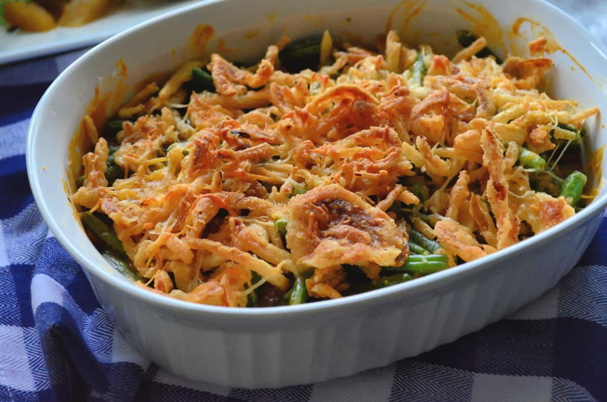 Golden Green Bean Casserole in a baking dish on a blue and white checkered cloth.