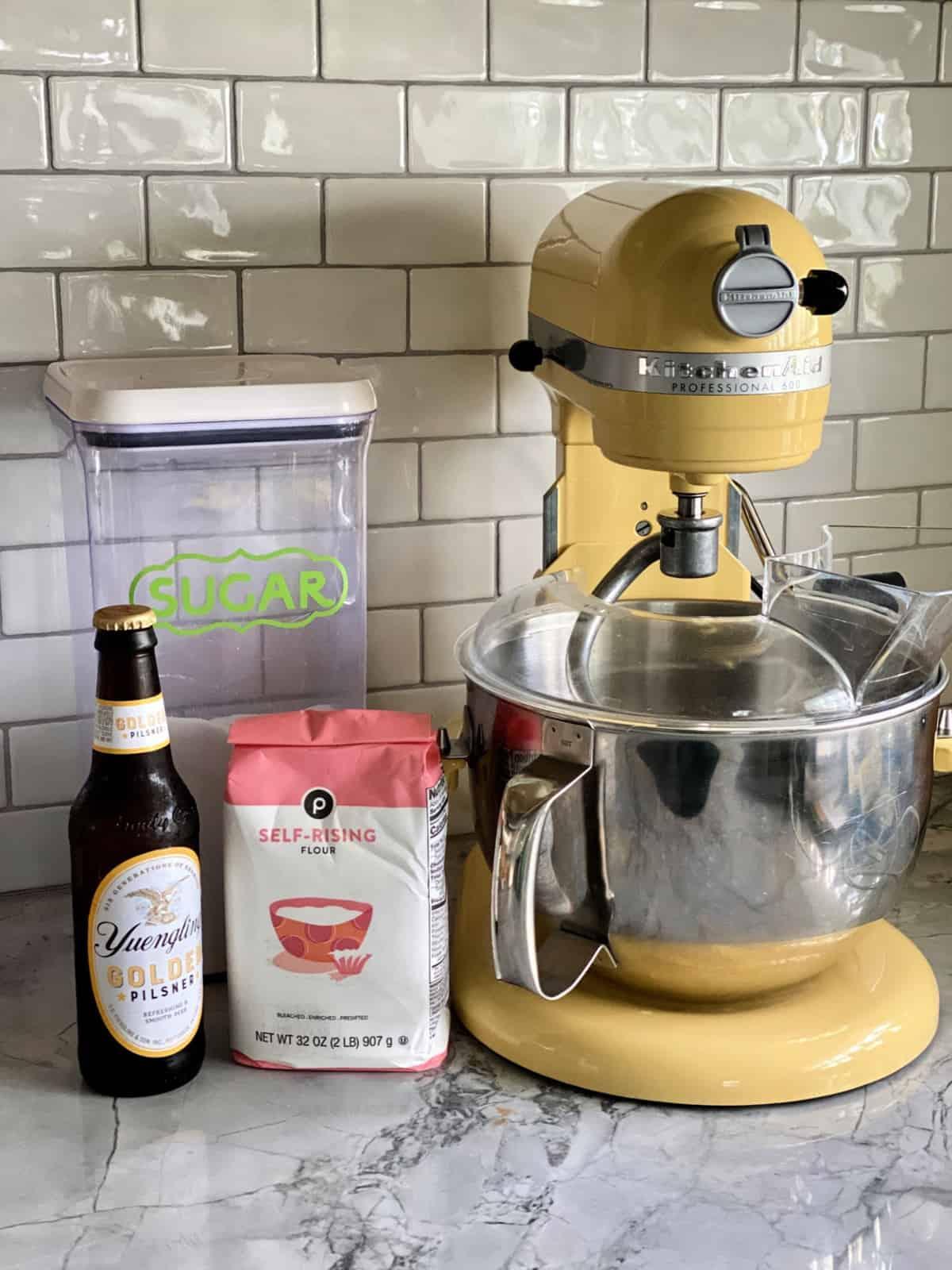 Yuengling Pilsner, self-rising Flour, and sugar on countertop next to yellow KitchenAid Professional 600 mixer.