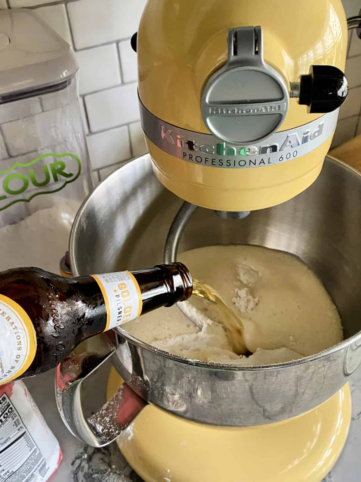 Pouring beer into beer bread batter in a mixing bowl