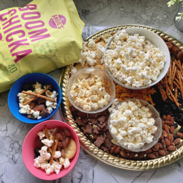 Angie's Boom Chicka Pop Sea Salt Pop Corn bag next to snack board.