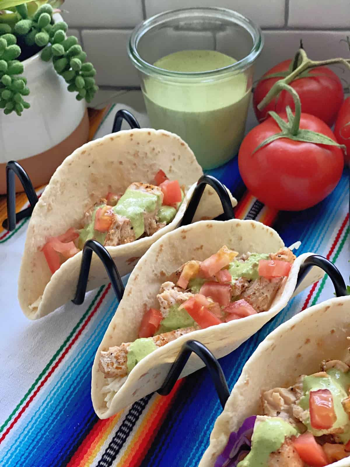 3 Blackened Swordfish Tacos in wire holder with glass of cilantro dressing and tomatoes in background.
