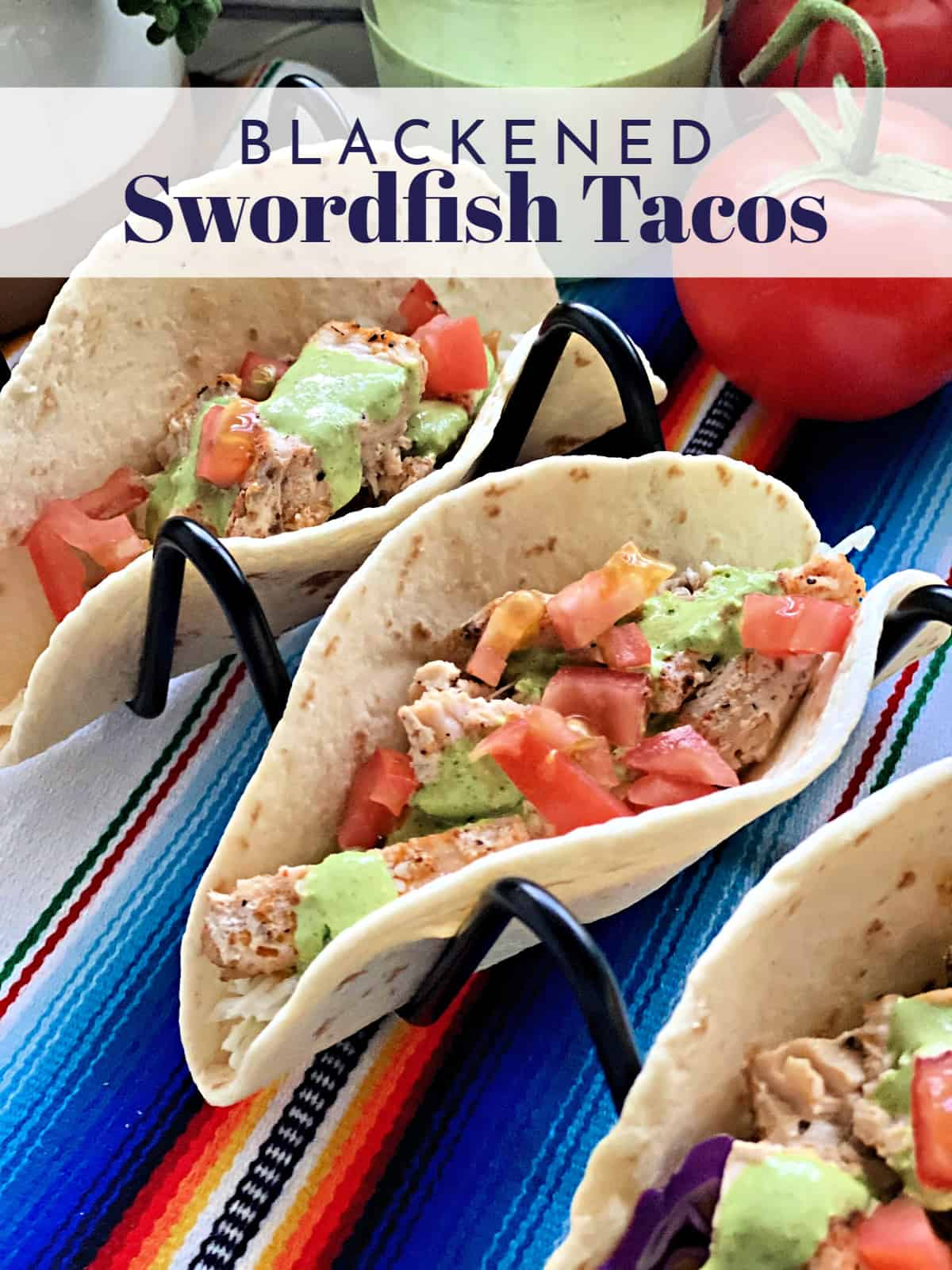 two fish tacos topped with tomatoes and cilantro dressing in wire holders with title text.