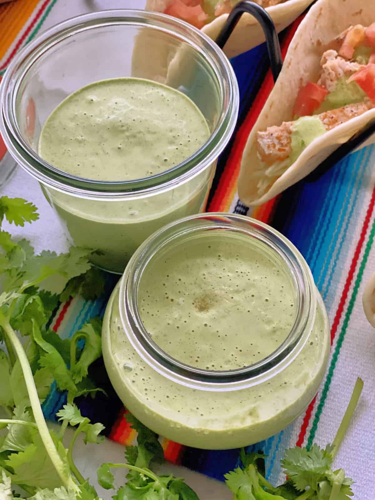 two jars of creamy light green liquid on colorful tablecloth with fresh cilantro and fish tacos.