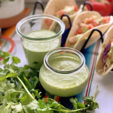 Close-up of 2 glasses of Blended Creamy Cilantro Dressing decoratively placed near cilantro.