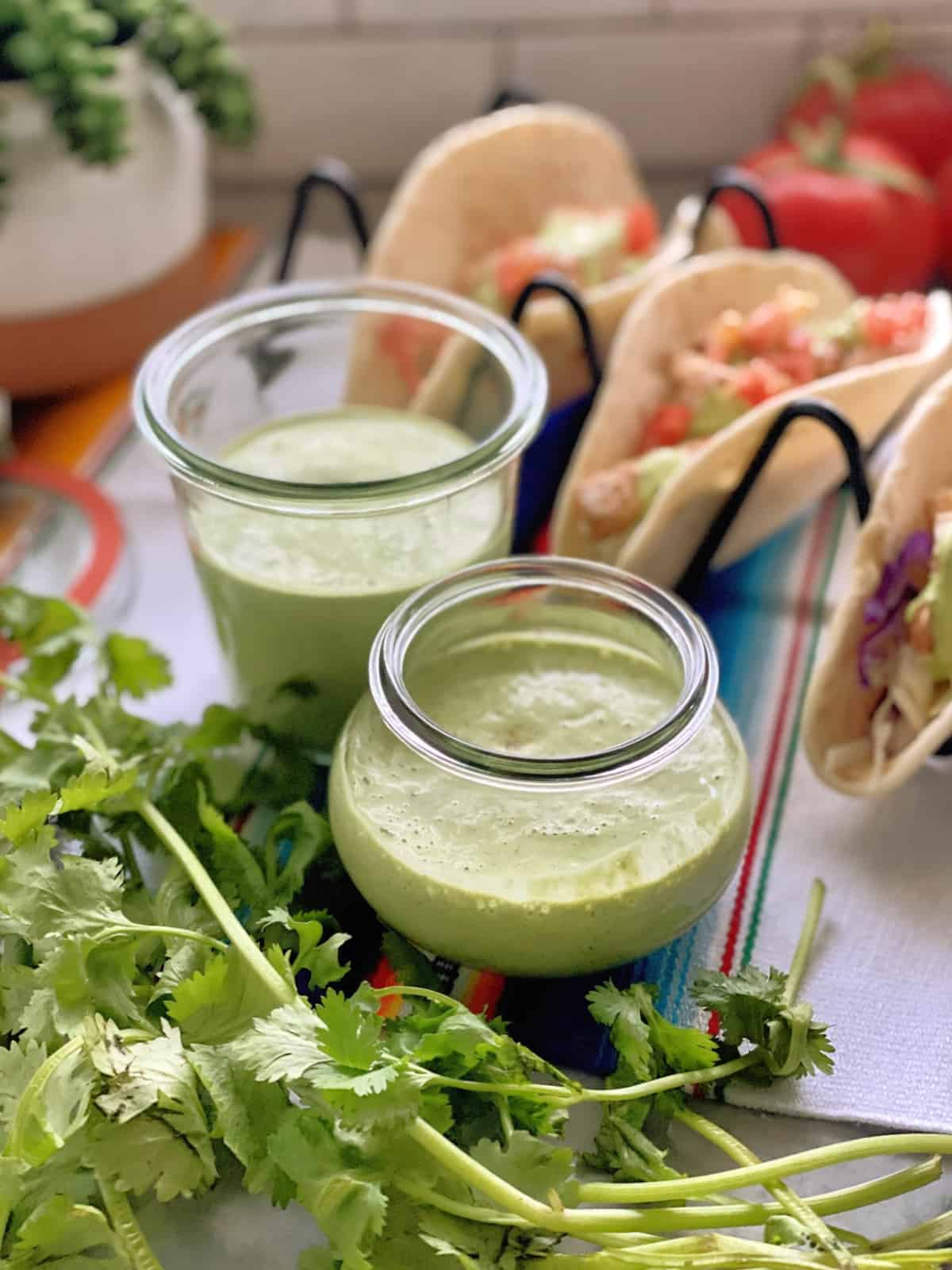 two jars creamy cilantro dressing on colorful tablecloth with fresh cilantro near and fish tacos behind.