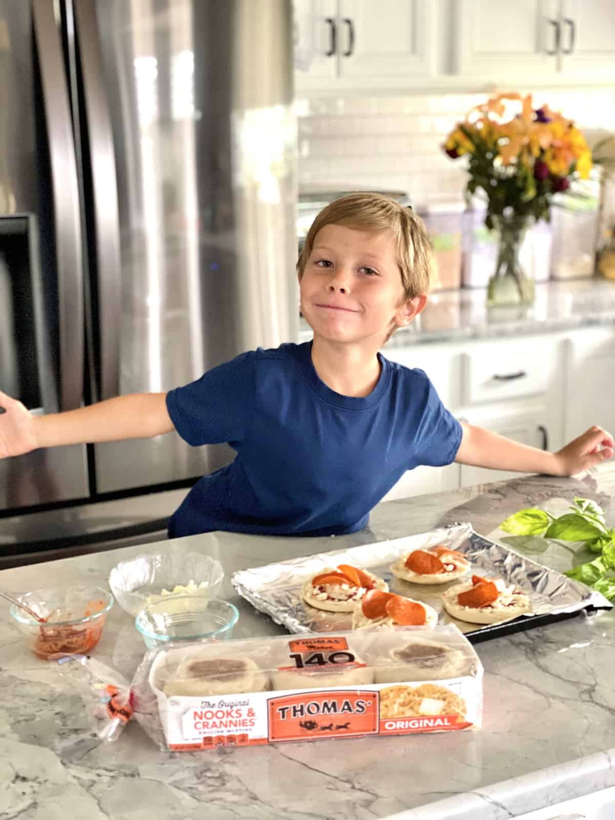 Little Boy making Toaster Oven English Muffin Pizzas on aluminum foil covered pan with ingredients displayed.