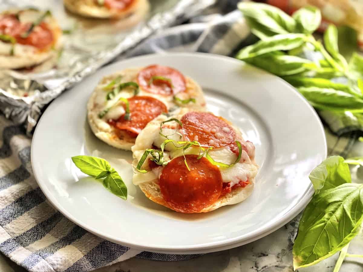 Cooked English Muffin Pepperoni Pizzas on white plate garnished with basil.
