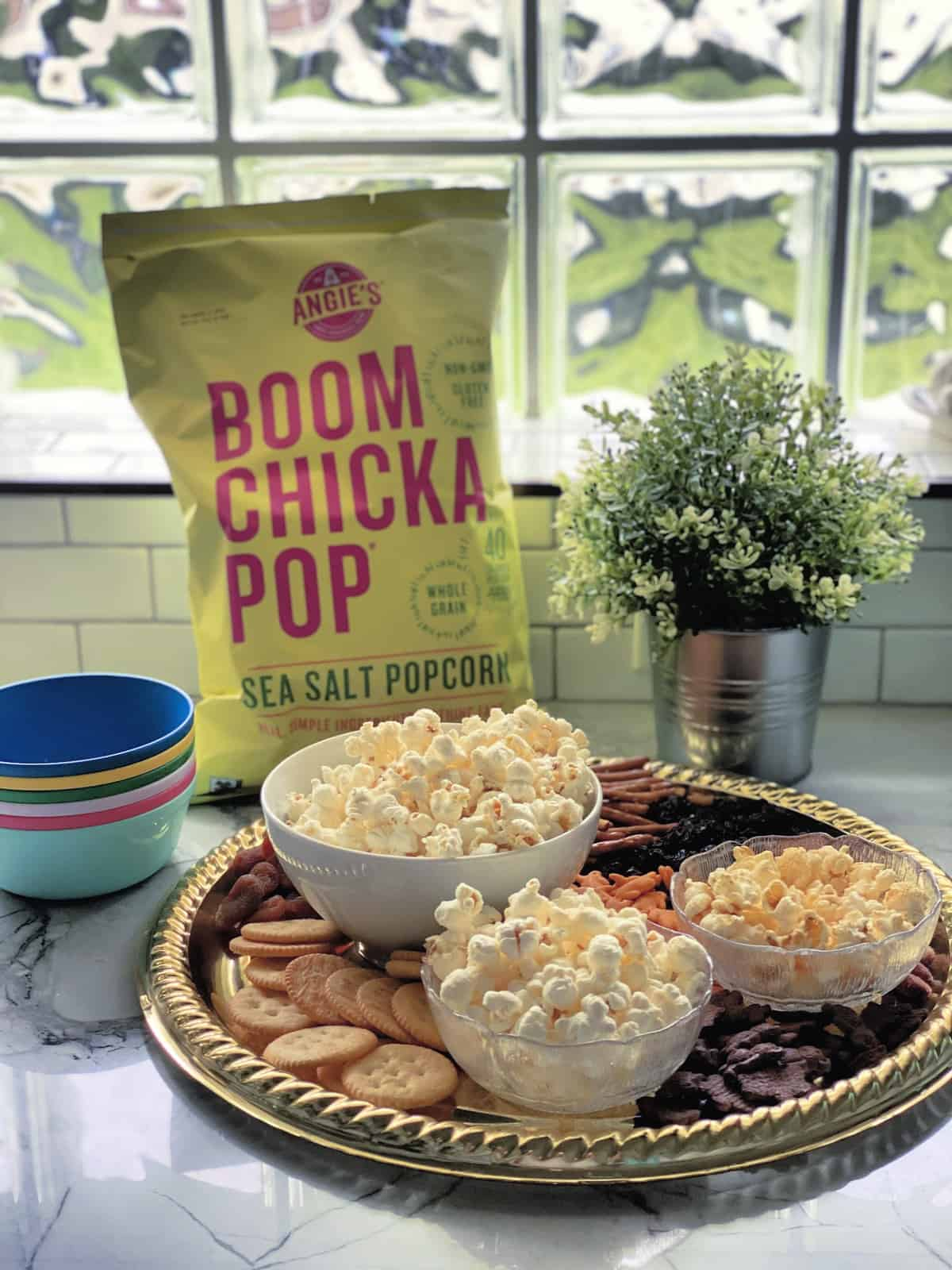 Platter with crackers, pretzels, dried fruits, and 3 bowls of popcorn in front of bag of boom chicka pop.