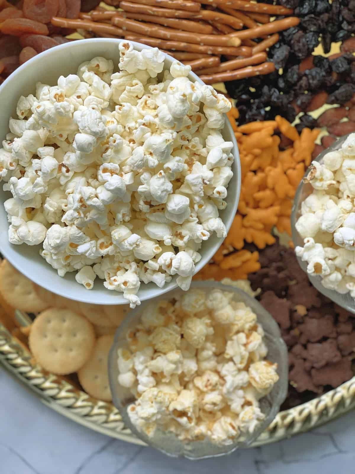 Close up top view of bowl of popcorn with pretzels, crackers, and dried fruits blurred on platter below.