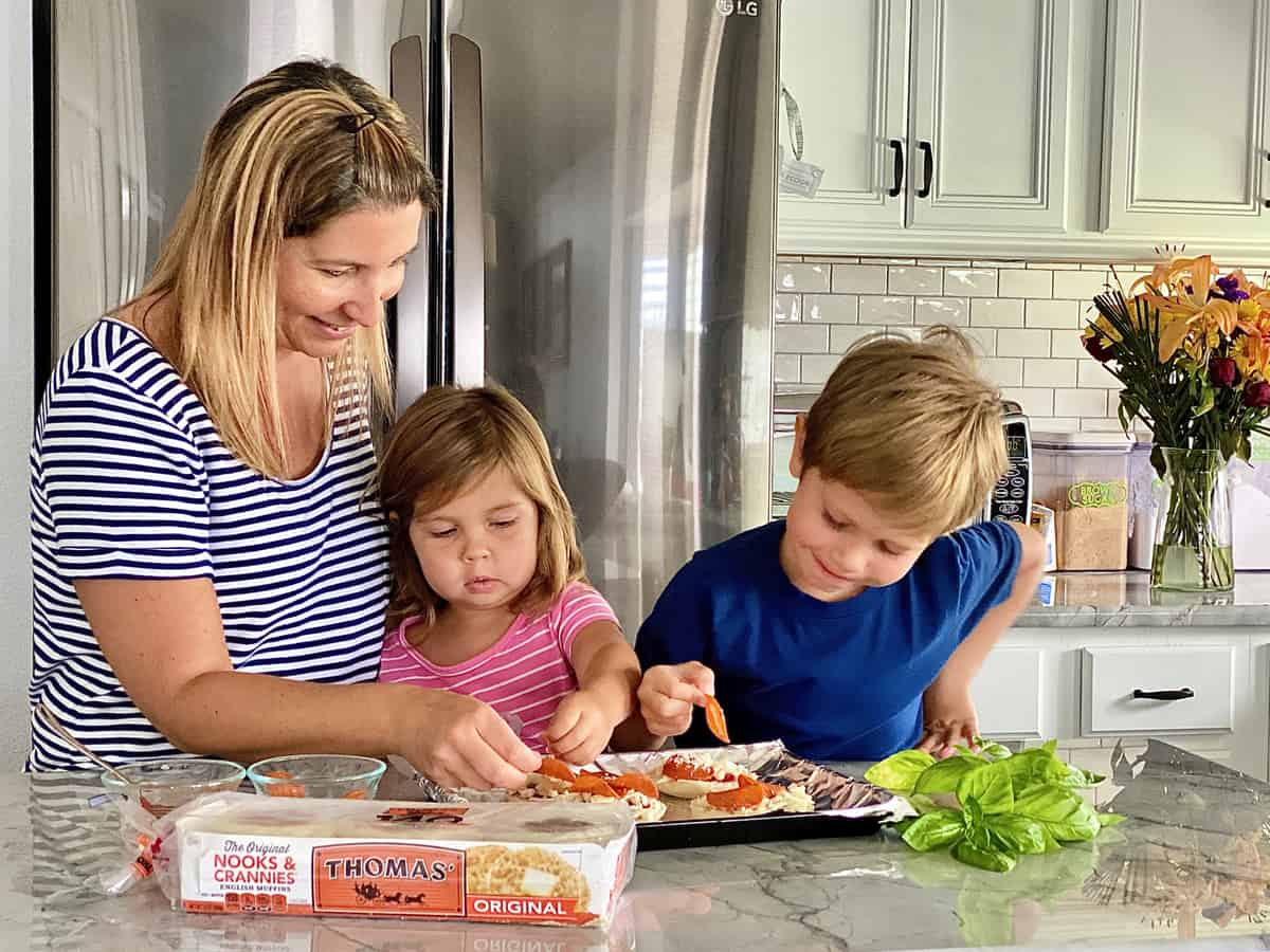 Mother, Daughter, and Son making Toaster Oven English Muffin Pizzas on aluminum foil covered pan.