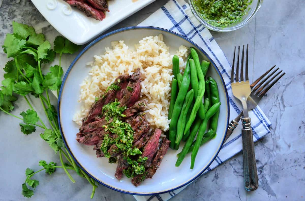top view of plated Grilled Skirt Steak with Chimichurri Sauce with green beans over rice bed.
