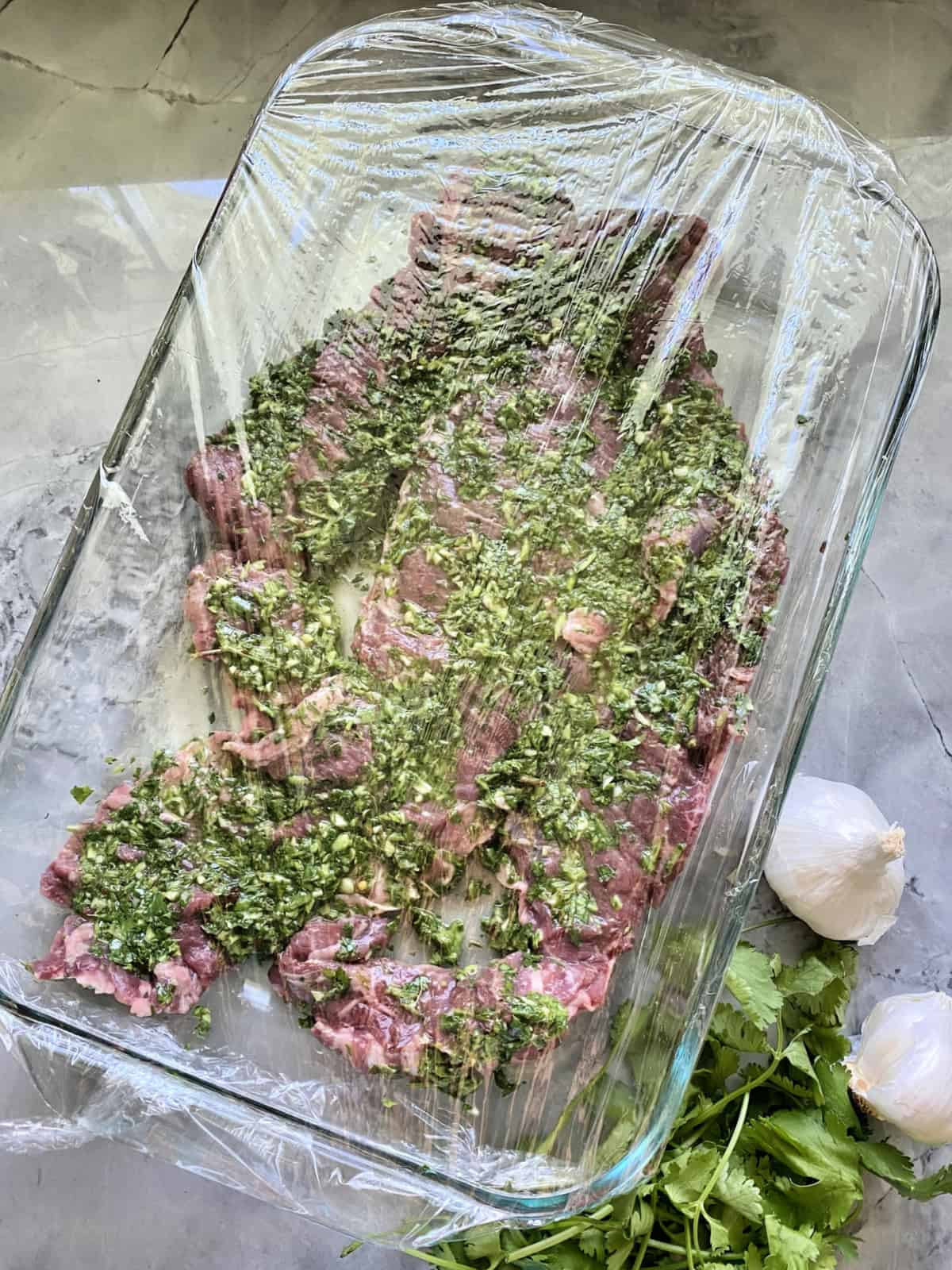 top view Grilled Skirt Steak with Chimichurri Sauce marinating in glass dish with saran wrap over top.