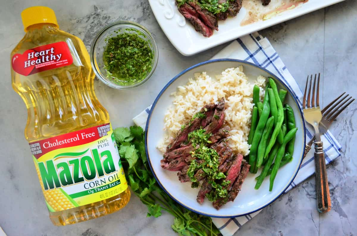 plated Skirt Steak with Chimichurri Sauce with green beans over rice bed near mazola corn oil bottle.