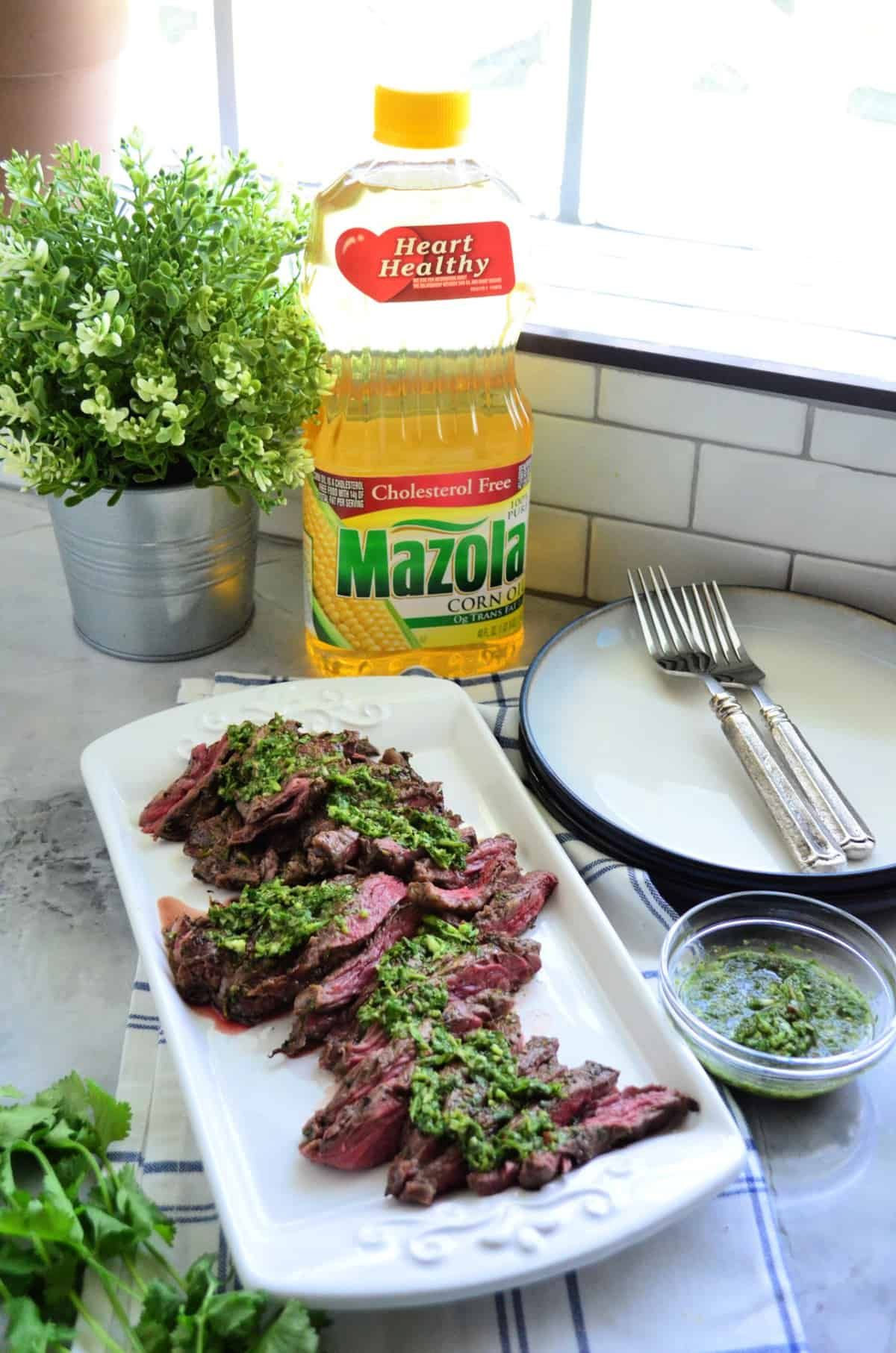 platter of sliced Grilled Skirt Steak topped with Chimichurri Sauce in front of Mazola Corn Oil.