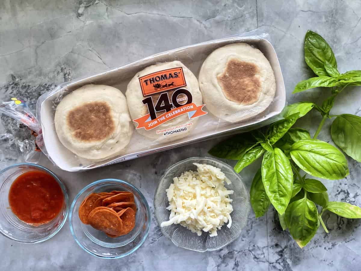 English Muffins, Tomato Sauce, Pepperoni, Mozzarella Cheese, and Basil to make Toaster Oven English Muffin Pizzas.