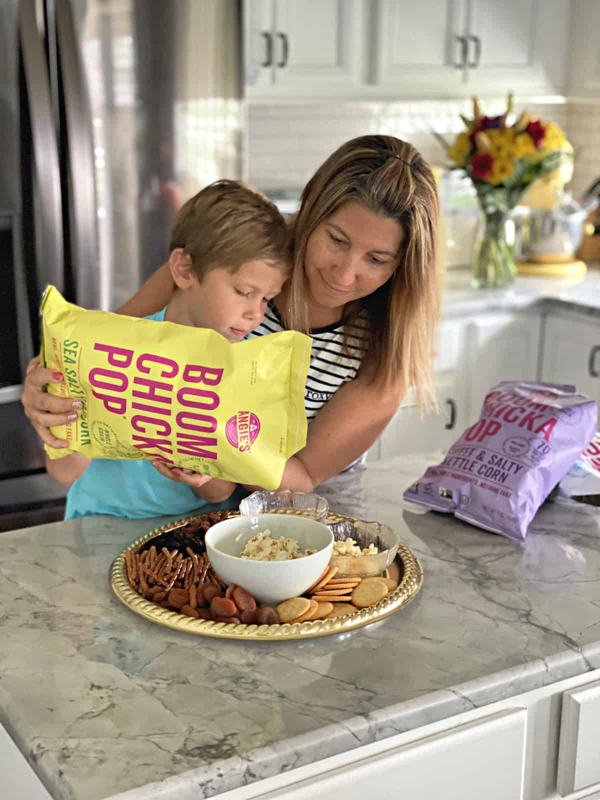 Mother and Son at kitchen counter putting together Snack Board by adding popcorn.
