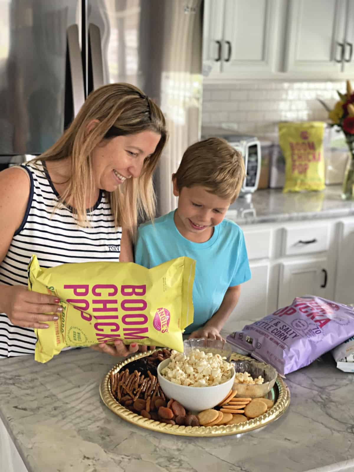 Mother and son pouring Angie's BOOMCHICKAPOP Sea Salt Popcorn into a bowl at countertop.