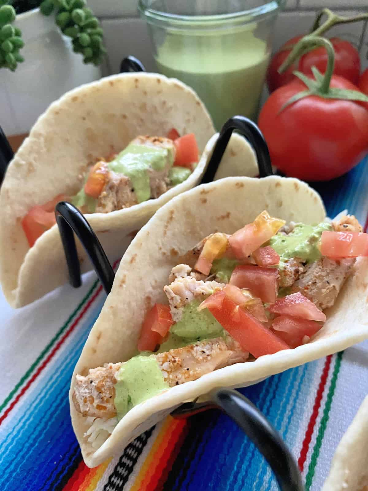 closeup of two fish tacos topped with tomatoes and cilantro dressing in wire holders on colorful tablecloth.