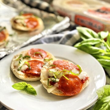Two Toaster Oven English Muffin Pizzas garnished with basil on a white plate over checkered tablecloth.