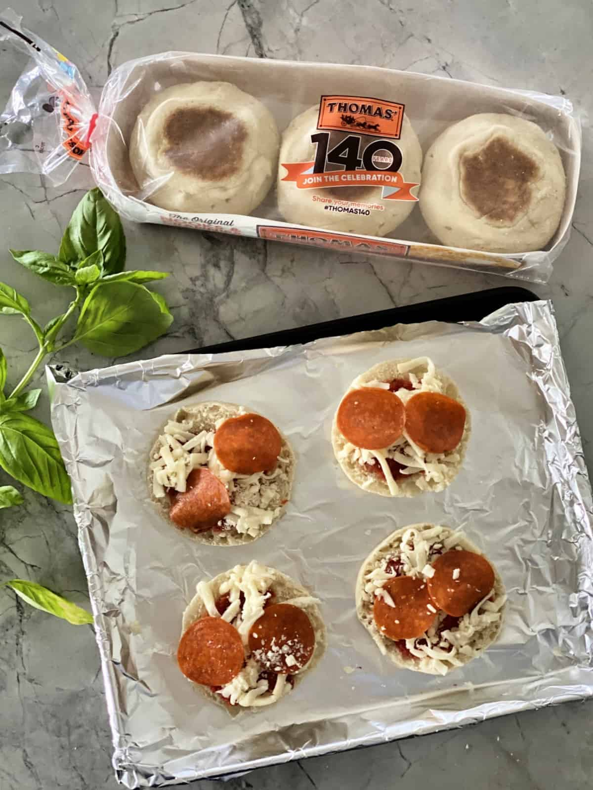 Toaster Oven English Muffin Pizzas assembled on aluminum foil covered pan next to package of Thomas English Muffins.