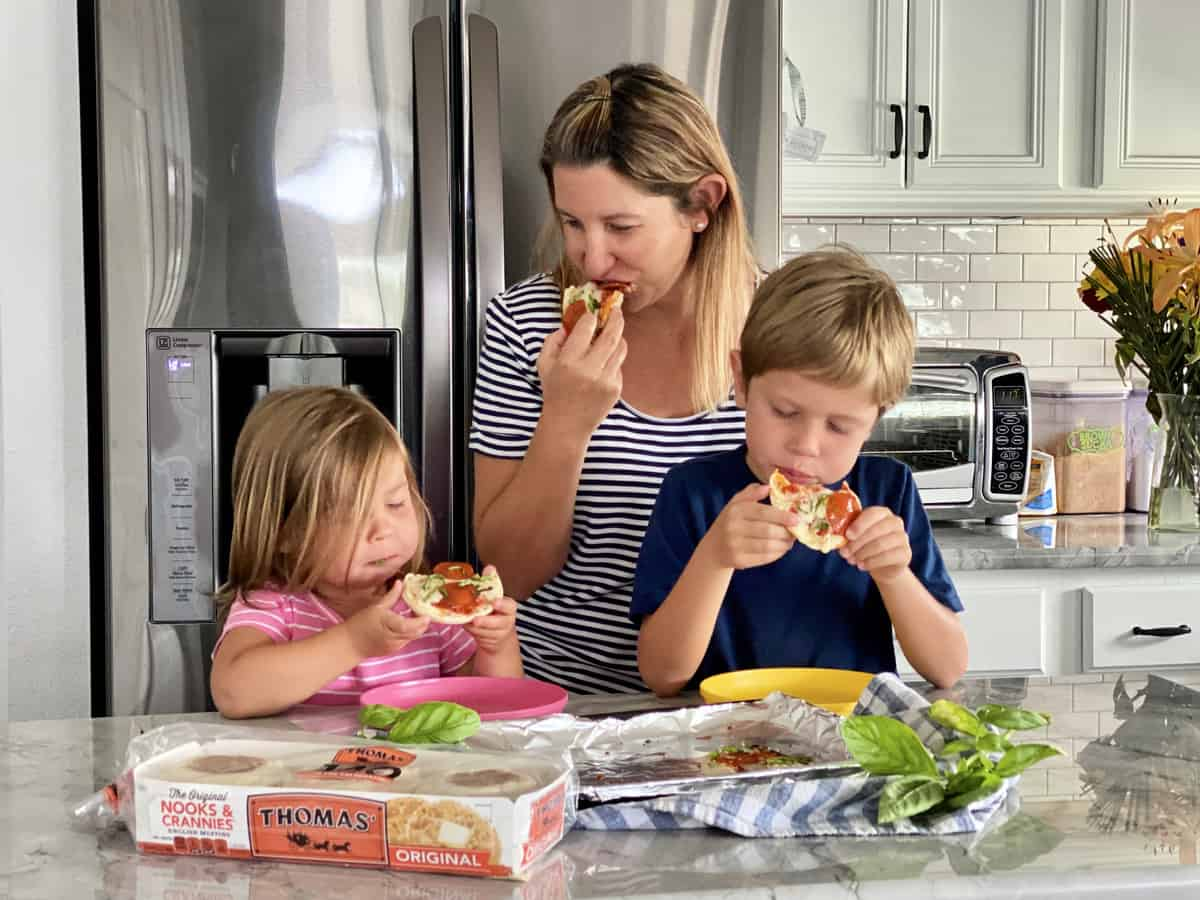 Mother and 2 children eating toaster oven english muffin pizzas over kitchen counter.