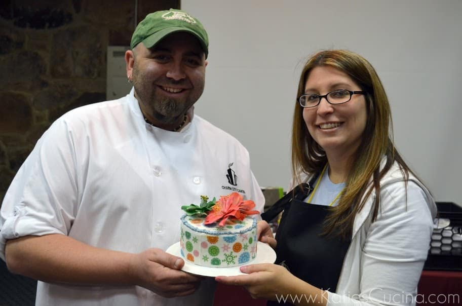 Blogger and Chef Duff Goldman smile holding polka-dot and snowflake decorated cake topped with poinsettias.