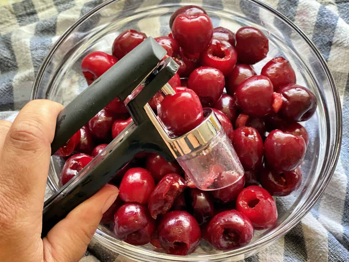Overhead shot with hand pressing fresh cherry through a pitter into a bowl of cherries.