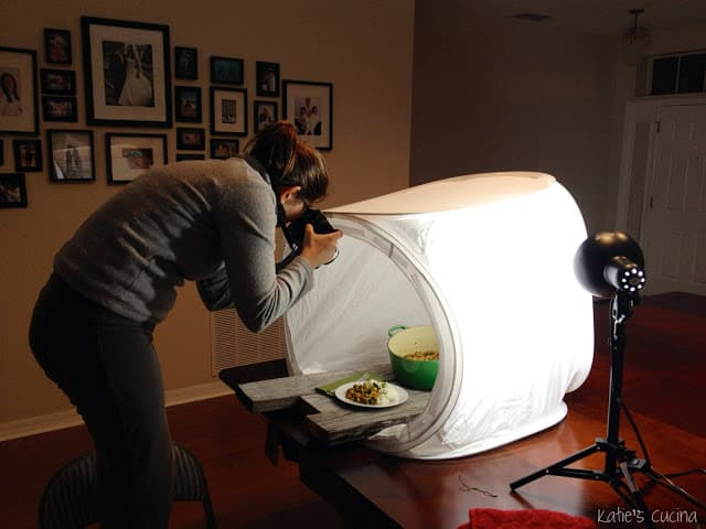Blogger photographing food in a white lightbox tent with artificial lighting.