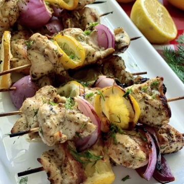 Chicken, red onion, and lemon on wood skewers on a white plate with fresh dill.