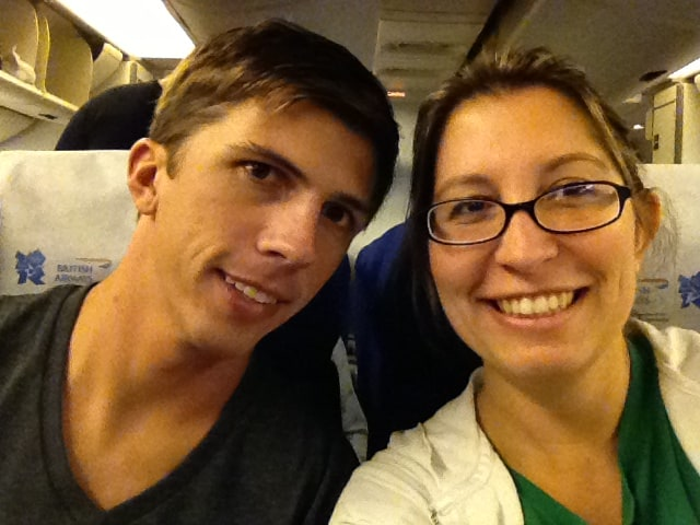 Selfie of Husband and blogger wife smiling while sitting on an airplane.