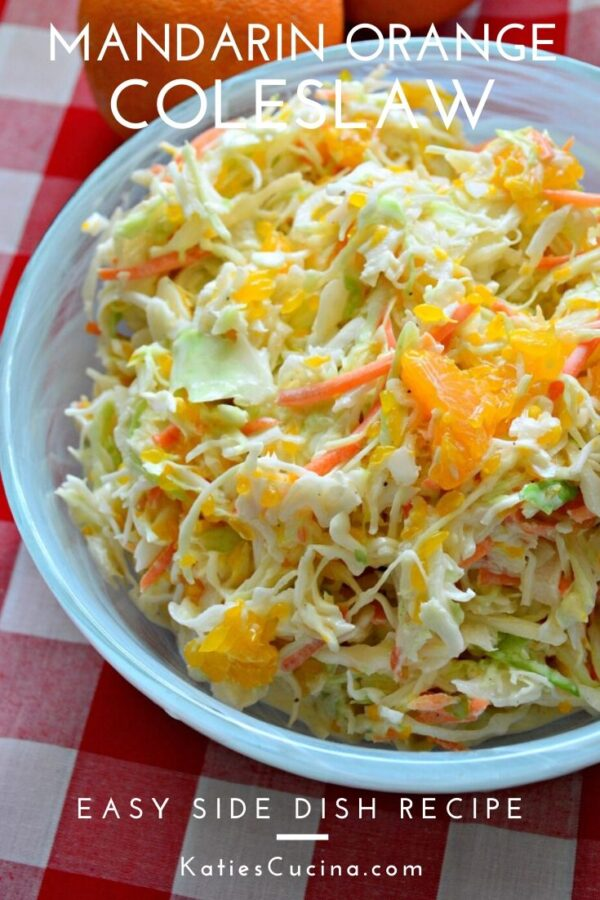 Close up of a top view of coleslaw with oranges in a blue bowl with text.