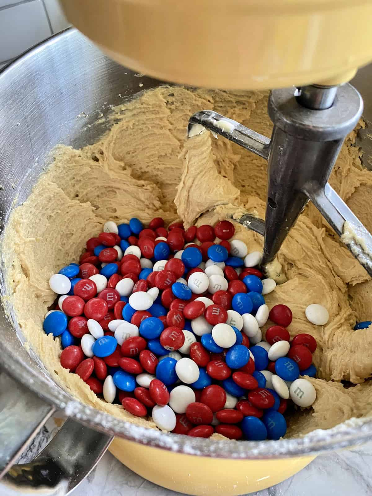 Red, white, and blue M&M's on tot of cookie dough  in a stand mixer.