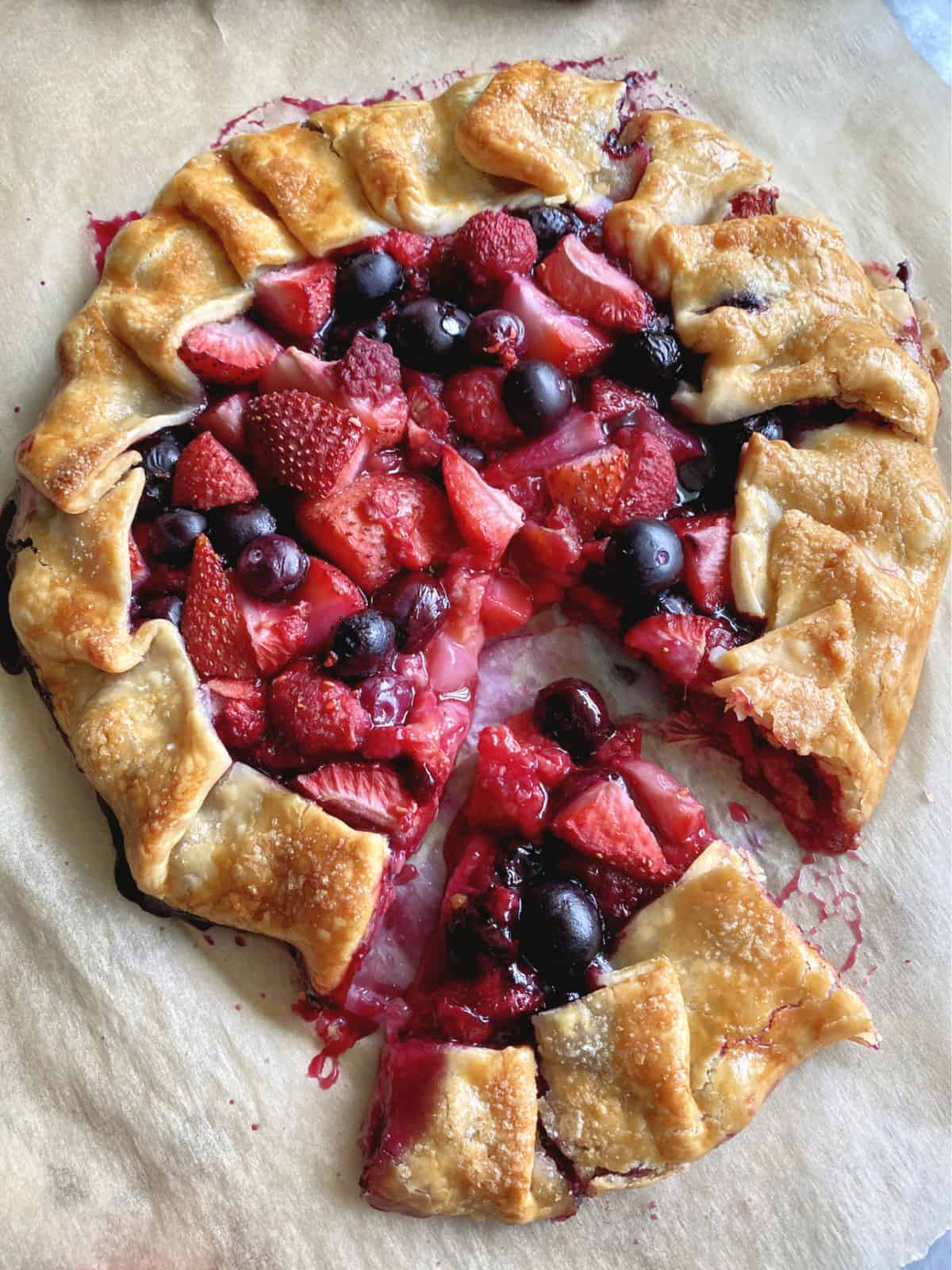 Top view of sliced open faced pie with berries and a slice cut out of it.
