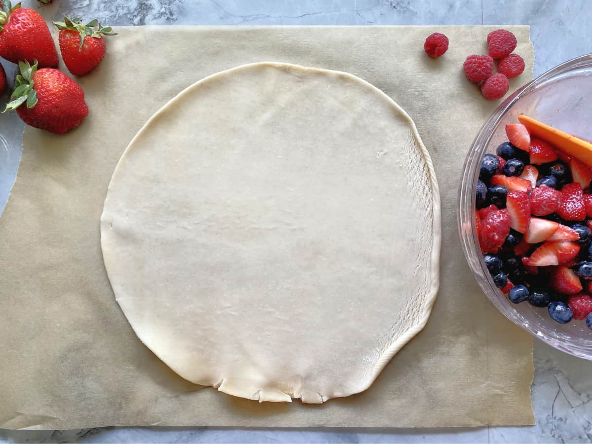 Pie dough rolled out on parchment paper with berries in bowl next to it.