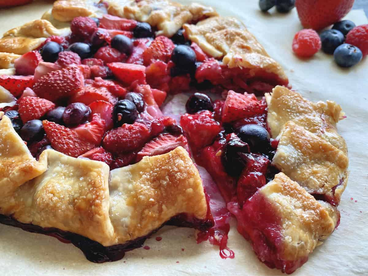 Cooked open faced pie with slice cut of strawberries, blueberries, and raspberries.