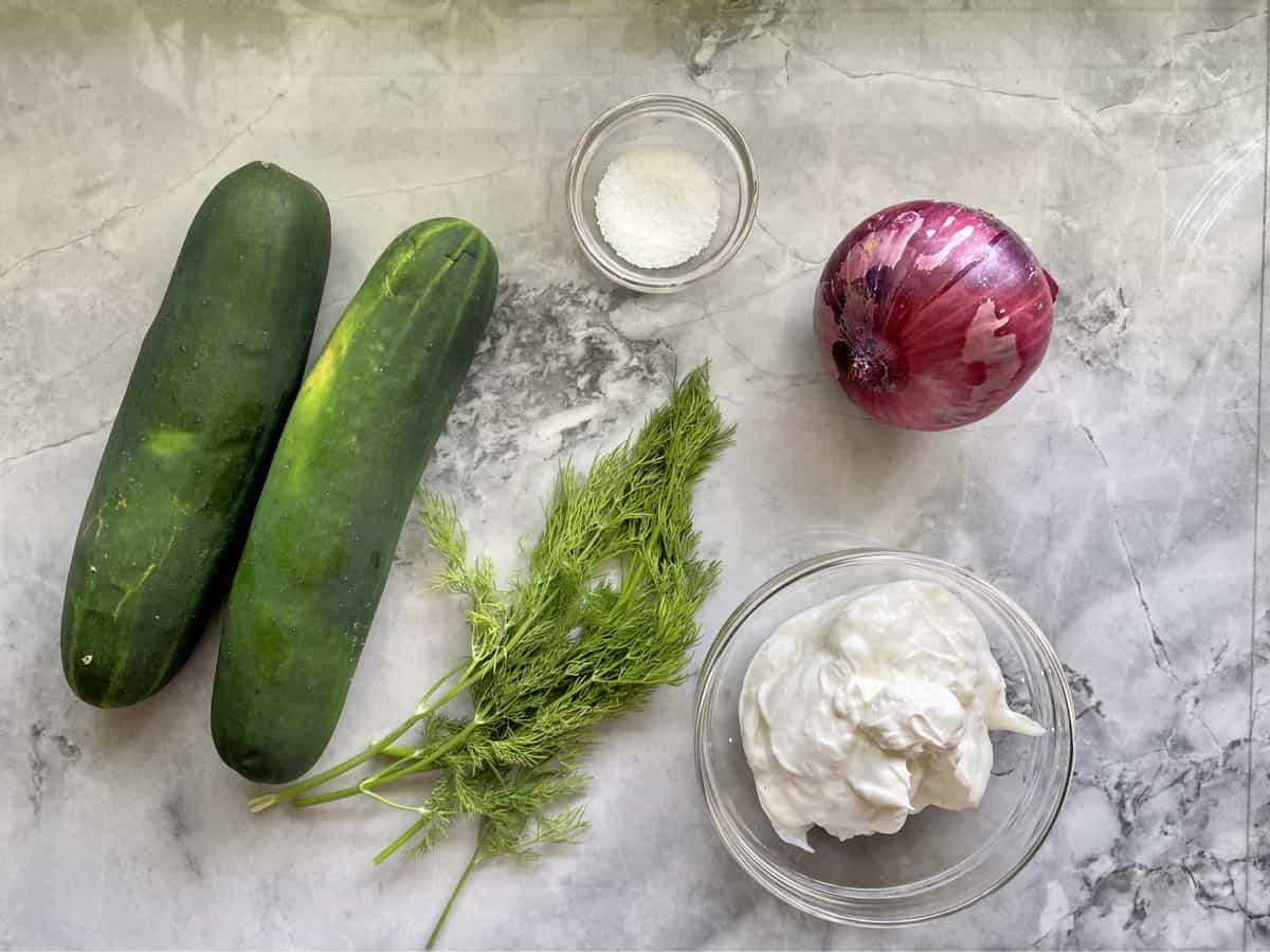 Ingredients on marble countertop: cucumber, fresh dill, salt, red onion, and sour cream.