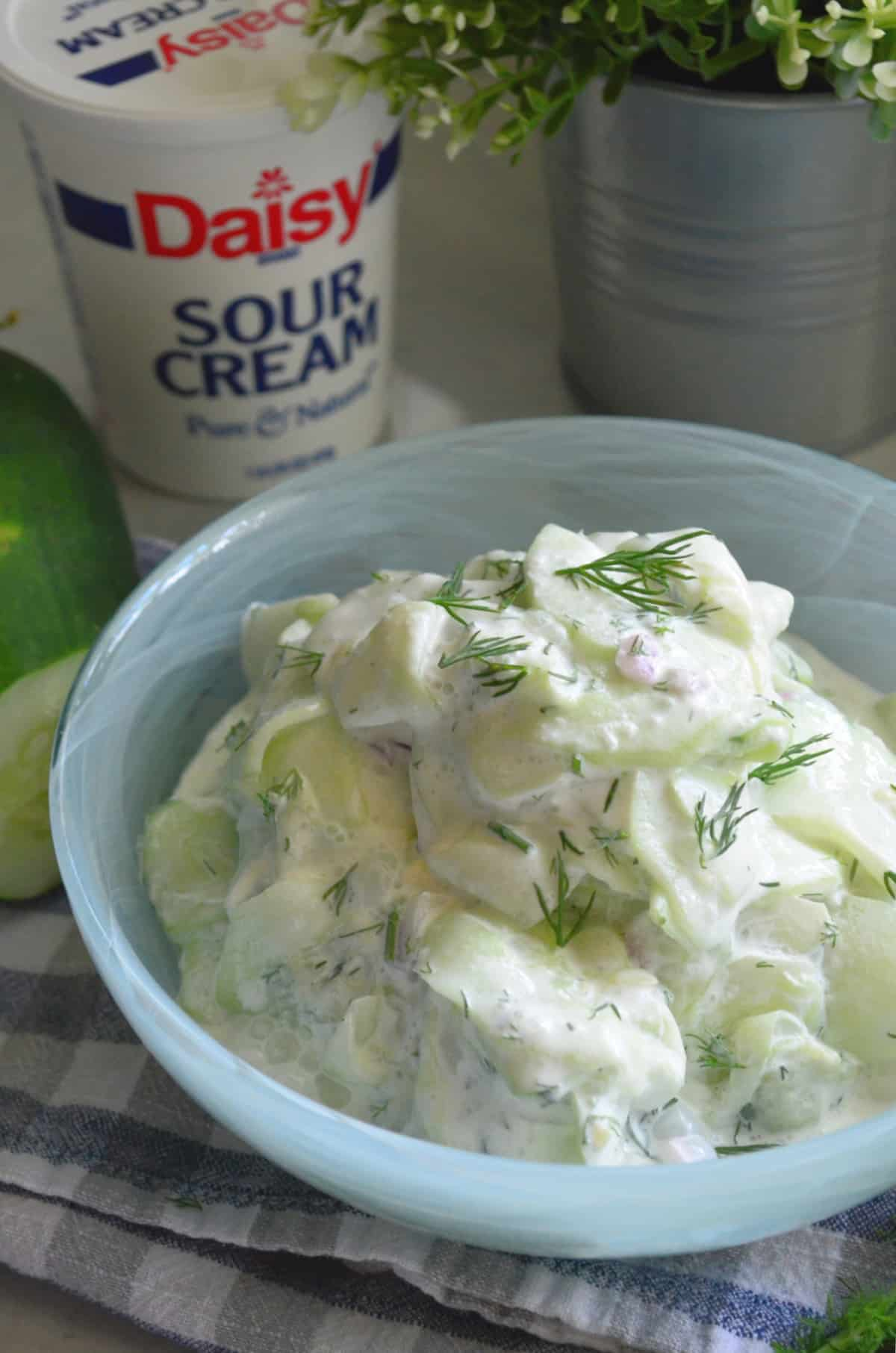Close up of thinly sliced cucumbers with sour cream, fresh dill and red onion in blue bowl.