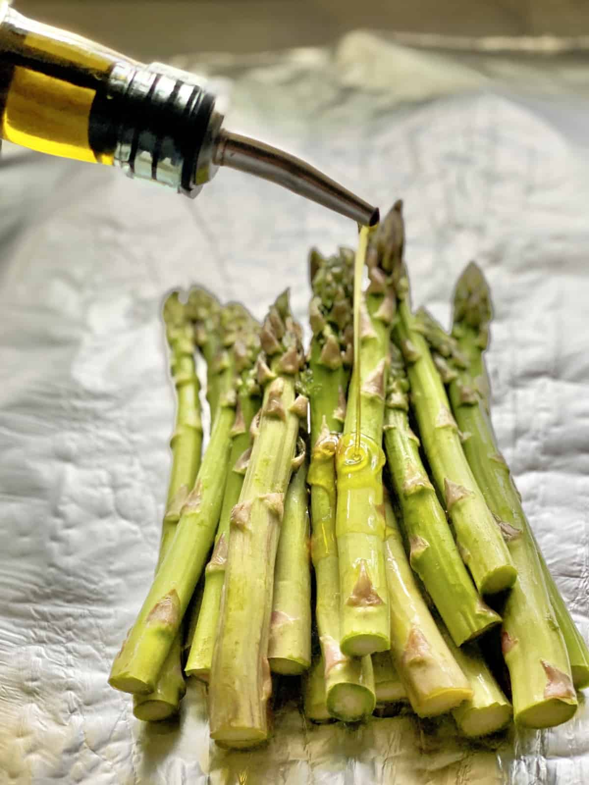 Bottle pouring oil on top of cut asparagus spears resting on foil.